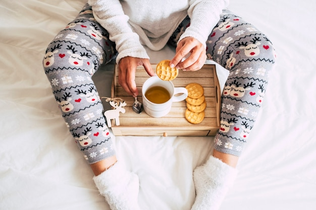 View of caucasian woman at home doing breakfast on the bed in winter season