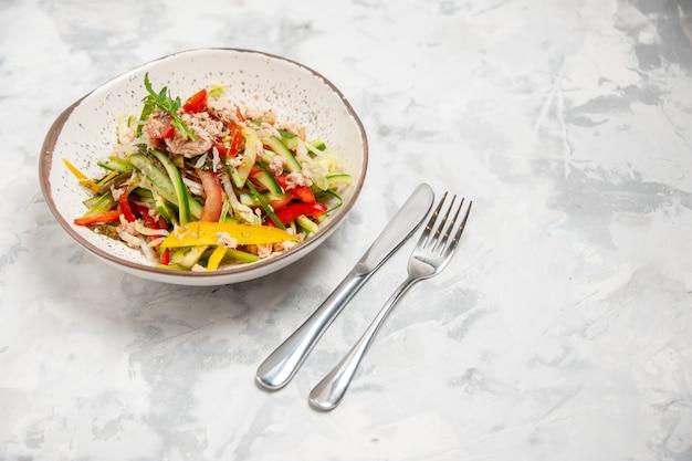 Vista dall'alto di insalata di pollo con verdure e posate su una superficie bianca macchiata
