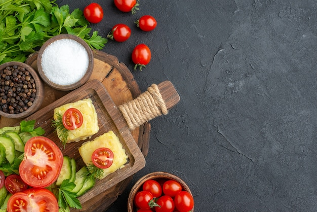 Sopra la vista del formaggio di verdure fresche tritate sul tagliere e del fascio di spezie verdi sul lato destro su superficie nera