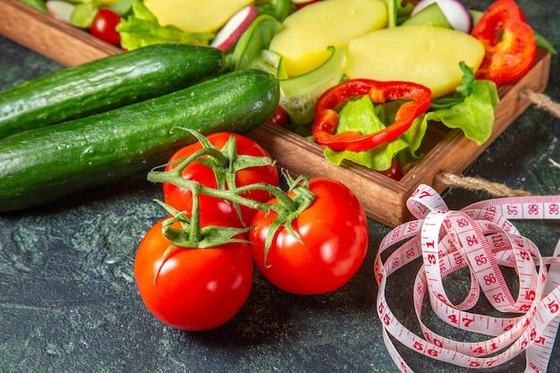 Sopra la vista di pomodori freschi di verdure tritate con misuratore di stelo e cetrioli su un vassoio di legno sulla superficie dei colori della miscela