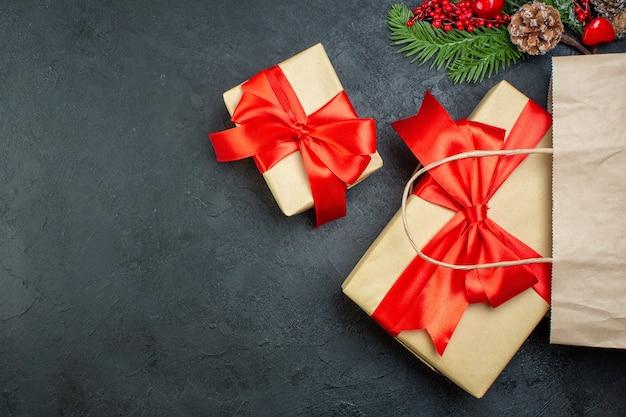 Sopra la vista dell'atmosfera natalizia con bellissimi doni e cono di conifere di rami di abete su sfondo scuro