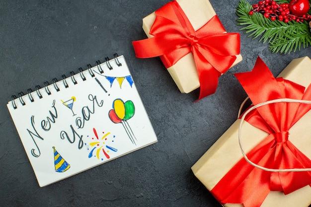 Sopra la vista dell'atmosfera natalizia con bellissimi doni e cono di conifere rami di abete accanto al taccuino su sfondo scuro