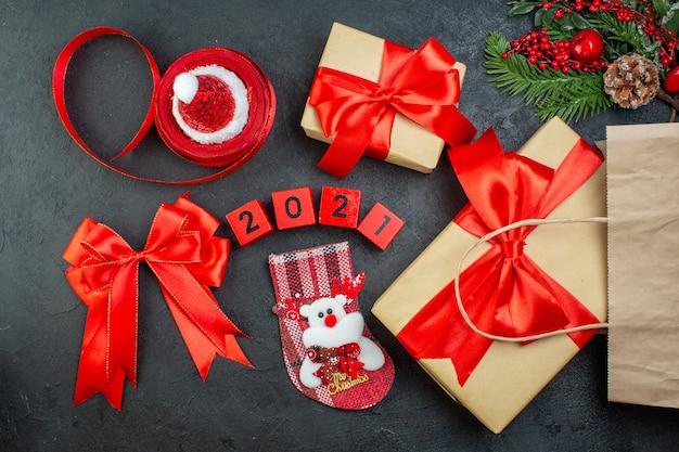 Sopra la vista dell'umore natalizio con bellissimi doni rami di abete cono di conifere nastro rosso e numeri cappello di babbo natale calza di natale su sfondo scuro