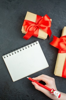 Above view of christmas mood with beautiful gifts and notebook with pen on dark background