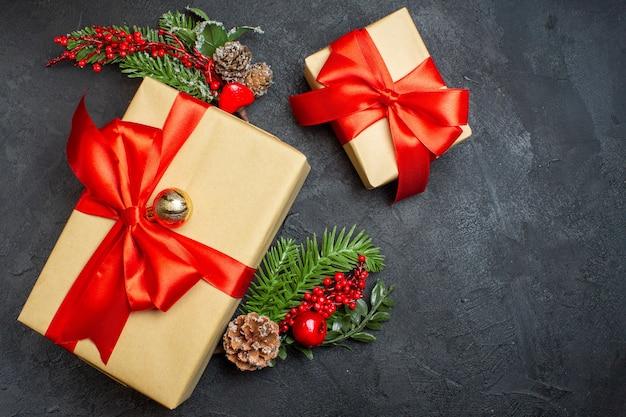 Sopra vista atmosfera natalizia con bellissimi regali con fiocco a forma di fiocco e accessori per la decorazione di rami di abete su uno sfondo scuro
