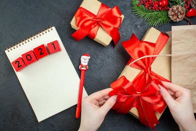 Sopra la vista dell'atmosfera natalizia con bellissimi regali con nastro rosso e numeri sul taccuino con la penna sul tavolo scuro