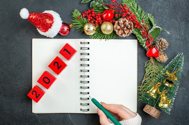 Above view of christmas mood with fir branches santa claus hat xsmas tree numbers on notebook on dark background