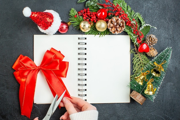 Sopra la vista dell'umore natalizio con il nastro rosso dell'albero di natale del cappello di babbo natale dei rami dell'abete sul taccuino su fondo scuro