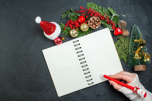 Above view of christmas mood with fir branches xsmas tree santa claus hat hand holding a pen on spiral notebook on dark background
