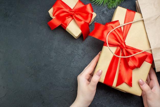 Sopra la vista dell'atmosfera natalizia con la mano che tiene bellissimi doni e cono di conifere di rami di abete su sfondo scuro