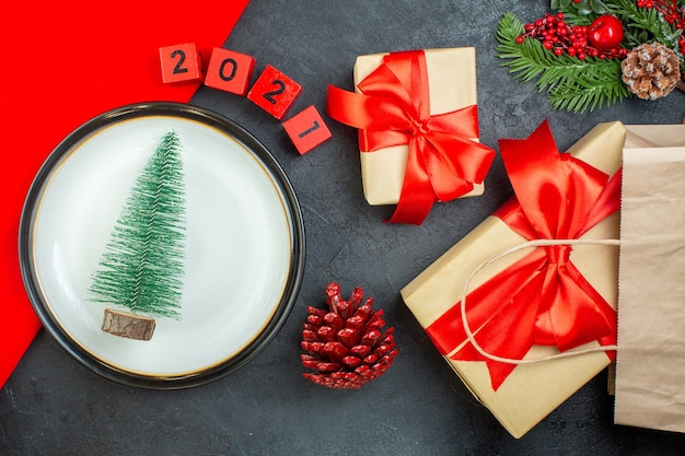 Above view of christmas tree on a plate conifer cone fir branches numbers beautiful gifts on a dark table