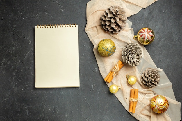 Above view of cinnamon limes decoration accessories and three conifer cones on nude color towel next to notebook on black color background