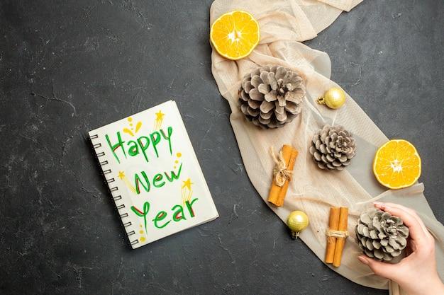 Sopra la vista di lime alla cannella e tre coni di conifere su taccuino di asciugamani di colore nudo con scritta felice vicino all'anno su sfondo di colore nero