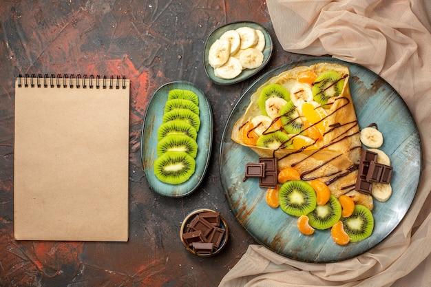 Sopra la vista degli agrumi in una deliziosa crepe decorata con salsa al cioccolato su un taccuino piatto blu su colori misti
