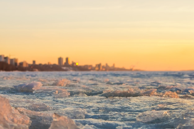 View of city in early spring in the sunset with ice pack in foreground and the city