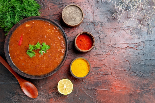 Above view of classic tomato soup in a brown bowl and different spices on mixed color table