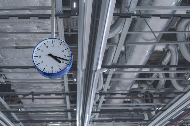 View of the clock that hangs from the ceiling against of ventilation pipes.