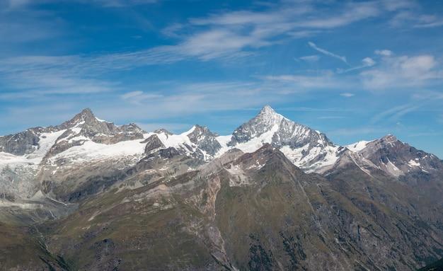 Просмотр сцены гор крупным планом в национальном парке церматт, швейцария, европа. летний пейзаж, солнечная погода, драматическое голубое небо и солнечный день