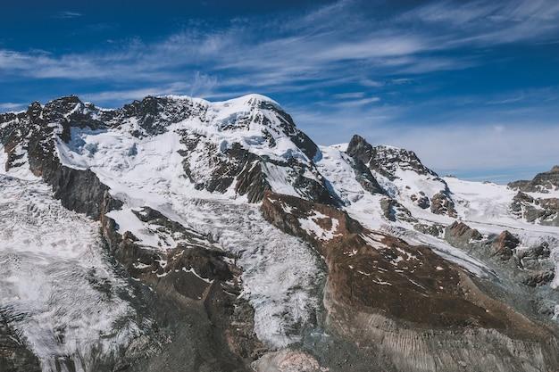 Посмотреть сцены гор крупным планом в национальном парке церматт, швейцария, европа. летний пейзаж, солнечная погода, драматическое голубое небо и солнечный день