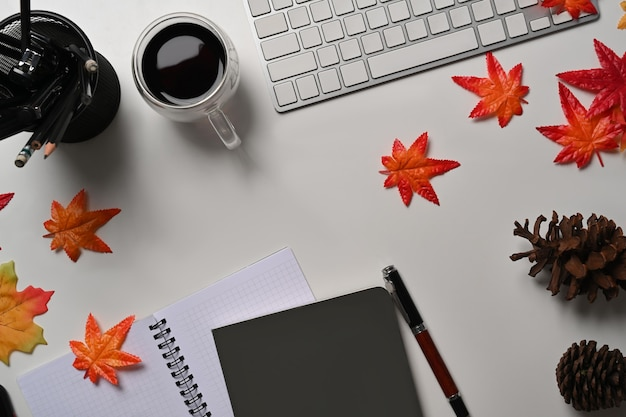 Above view coffee cup, pine cones, notebook and maple leaves on white background.