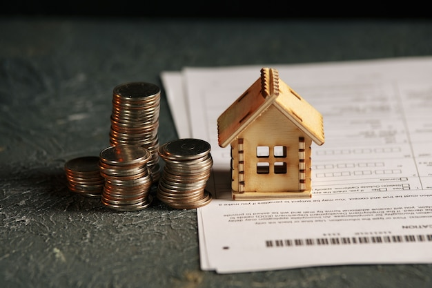 View of coin stack with house model on green