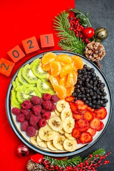 Above view of collection of fresh fruits on dinner plate decoration accessories fir branches and numbers christmas sock on a red napkin on a black background