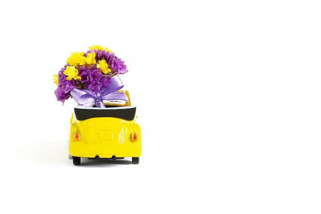 View of a colorful bouquet of purple flowers that is in a small yellow car . selective focus. the concept of a holiday, wedding, flower delivery, gift.