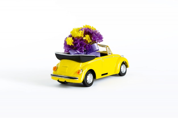 View of a colorful bouquet of purple flowers that is in a small yellow retro car . selective focus. the concept of a holiday, wedding, flower delivery, gift