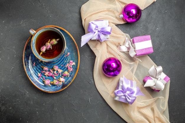 Sopra la vista di accessori per la decorazione di regali colorati per il nuovo anno su un asciugamano di colore nudo e una tazza di tè su sfondo nero