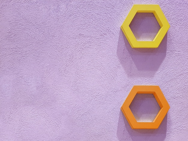 View of the concrete plastered wall of purple color on which decor elements in the form of hexagons hang from which hard shadows fall. concept for texture, , interior