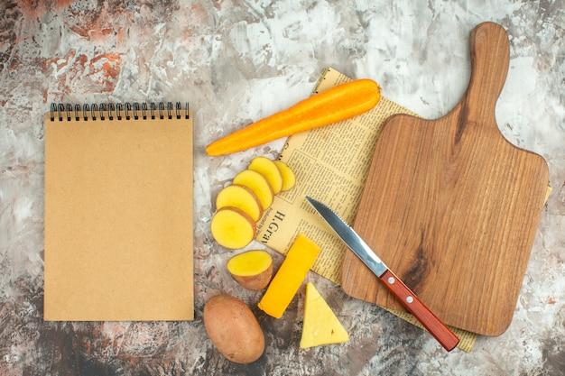 Above view of cooking background with various vegetables and two kinds of cheese knife and wooden cutting board on mixed color background