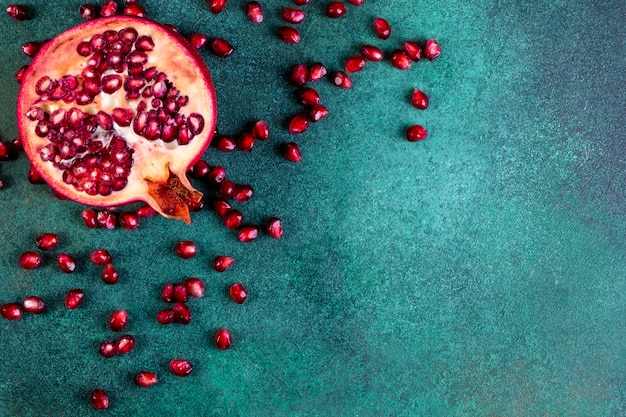 View  copy space chopped half pomegranate with peeled on a green table