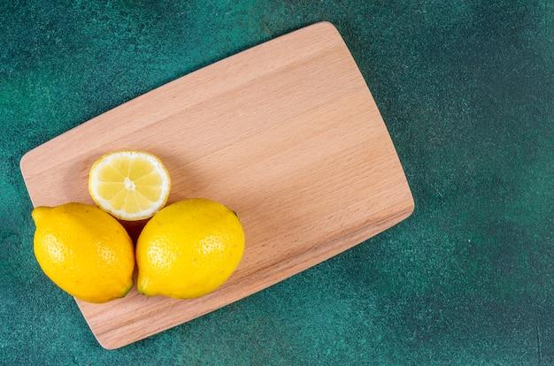 緑のテーブルの黒板にコピースペースレモンを表示します。