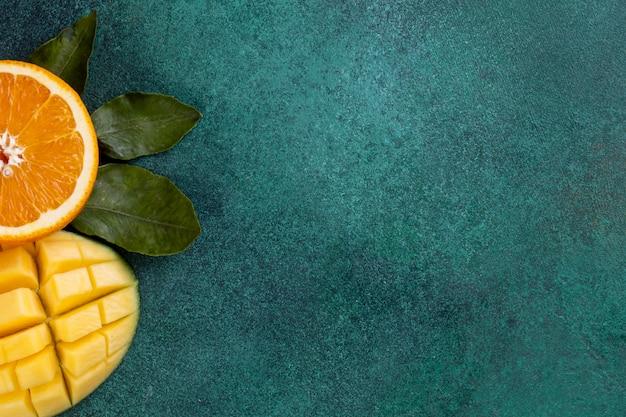 Просмотр копии пространства нарезанного манго с половиной апельсина на зеленом столе