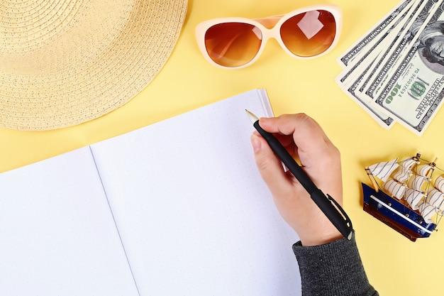 メモ帳の黄色の背景、サングラス、帽子、お金。トップview.copyスペース。夏の背景、旅行。