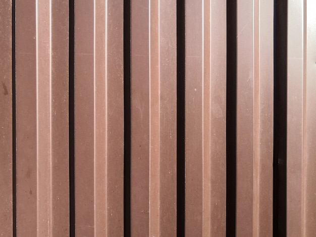 View of a corrugated brown iron sheet with vertical waves lit from the side in bright sunlight