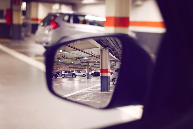 View of a covered parking trough the car mirror