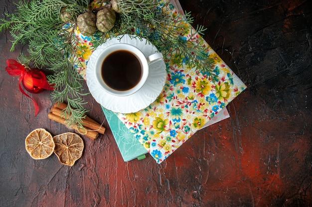 Sopra la vista di una tazza di tè nero su due libri, lime alla cannella e accessori per la decorazione di rami di abete su sfondo scuro