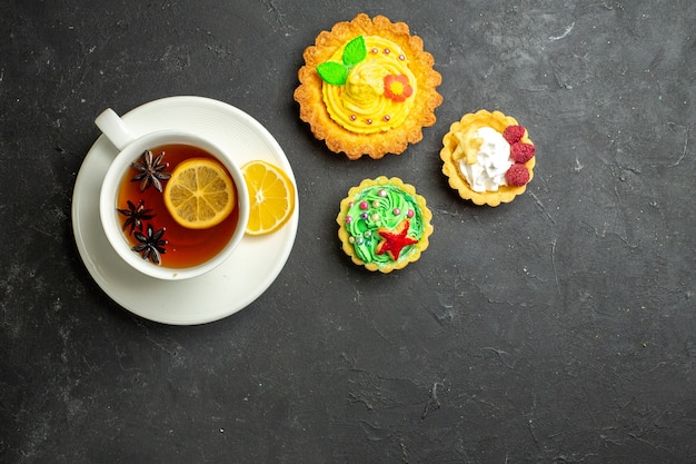 Sopra la vista di una tazza di tè nero al limone servita con biscotti su sfondo scuro