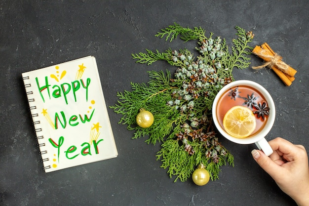 Above view of a cup of black tea xsmas accessories and cinnamon limes and notebook with happy new year inscription on black background