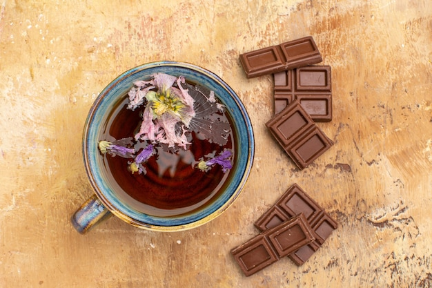 Above view of a cup of hot herbal tea and chocolate bars on mixed color table