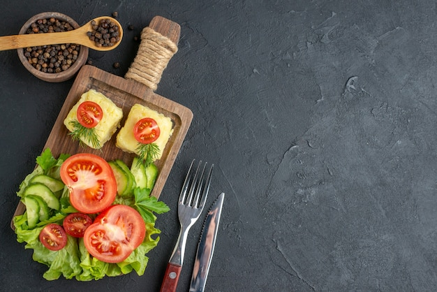 Above view of cut fresh tomatoes and cucumbers cheese on wooden board cutlery set on the right side on black surface