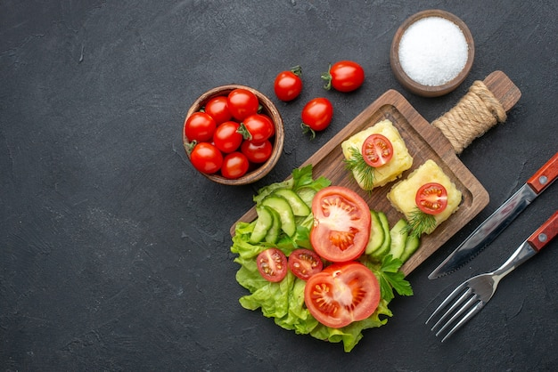Above view of cut fresh tomatoes and cucumbers cheese on wooden board cutlery set salt on black surface