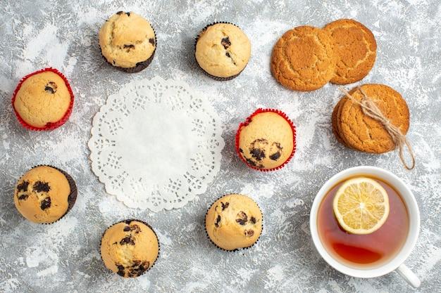 Sopra la vista del tovagliolo decorato tra deliziosi piccoli cupcakes con cioccolato e una tazza di tè nero con biscotti impilati al limone sulla superficie del ghiaccio