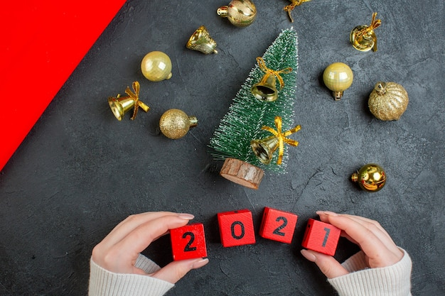 Above view of decoration accessories and christmas tree numbers on dark background