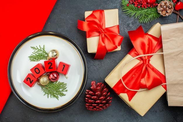 Sopra la vista di accessori di decorazione su un piatto cono di conifere rami di abete bellissimi regali con nastro rosso su un tavolo scuro