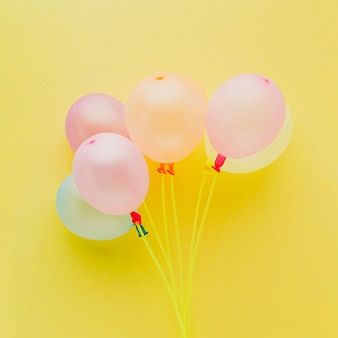 Above view decoration with balloons on yellow background