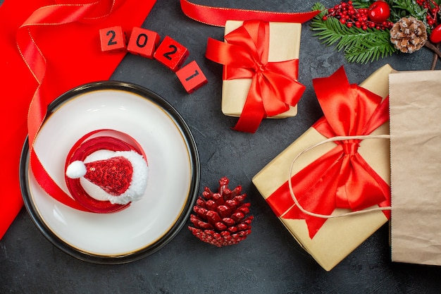 Sopra la vista della deliziosa torta su un piatto cono di conifere rami di abete numeri bei regali su un tavolo scuro