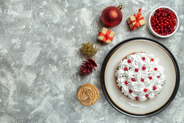 Above view of delicious cake with cream currant on a plate and gift boxes stacked cookies conifer cones on the left side on gray background