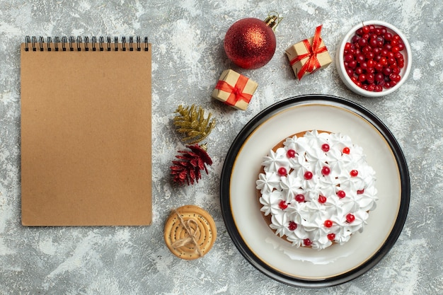 Above view of delicious cake with cream currant on a plate and gift boxes